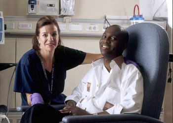 """""""Nurse poses with cancer patient"""" by Rhoda Baer and the National Cancer Institute (NCI) (via Wikimedia Commons) is licensed under CC0"""