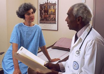 """Doctor Consults with Patient"" by the National Cancer Institute (via Wikimedia Commons) is licensed under CC0"