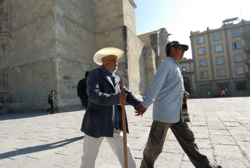 """Assisting blind man walking mexico"" by milio labrador (via Wikimedia Commons) is licensed under Creative Commons Attribution 2.0 Generic"