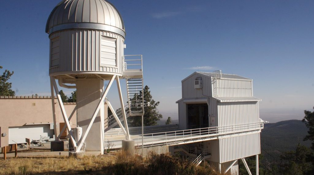 The NMSU 1-meter telescope structure, with the Sloan Telescope housing in the background. Image Credit: Maurice Clark and the Sloan Digital Sky Survey. License: Standard SDSS image license CC-BY via www.sdss.org